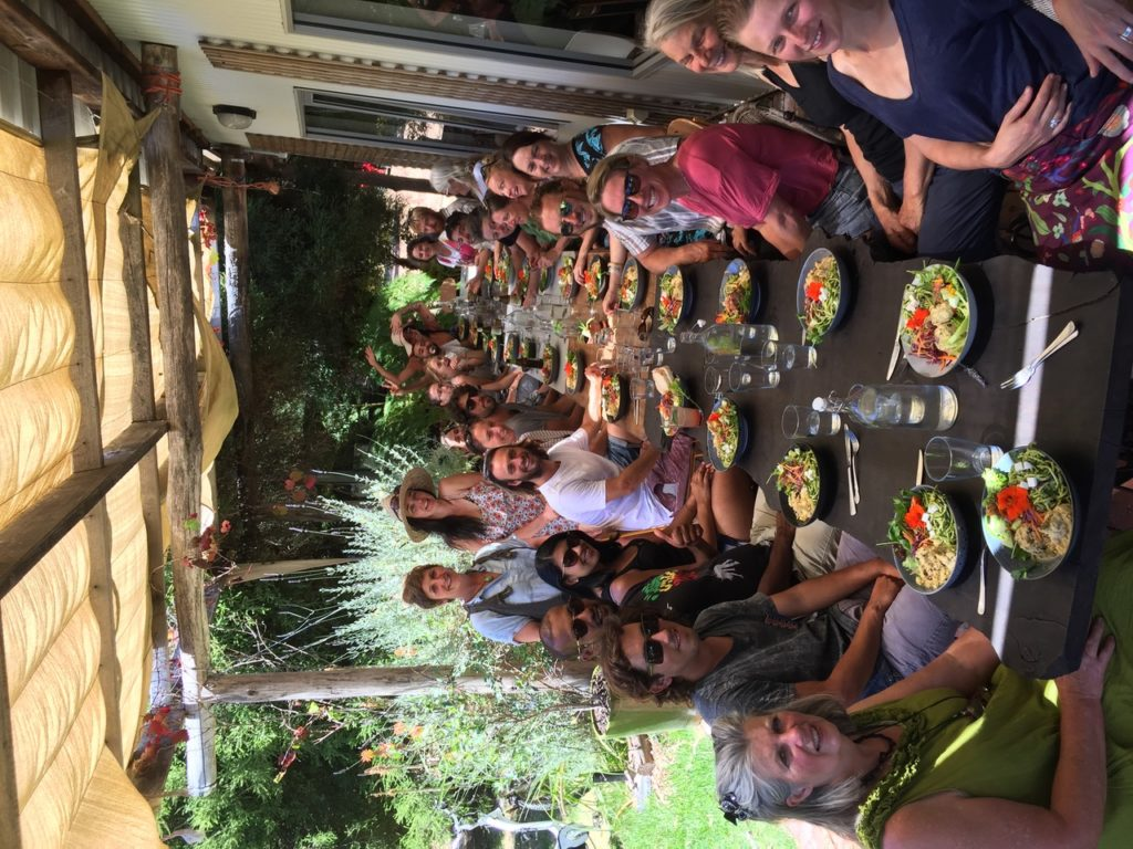 Group of people seated around a long wooden table eating vegetarian food